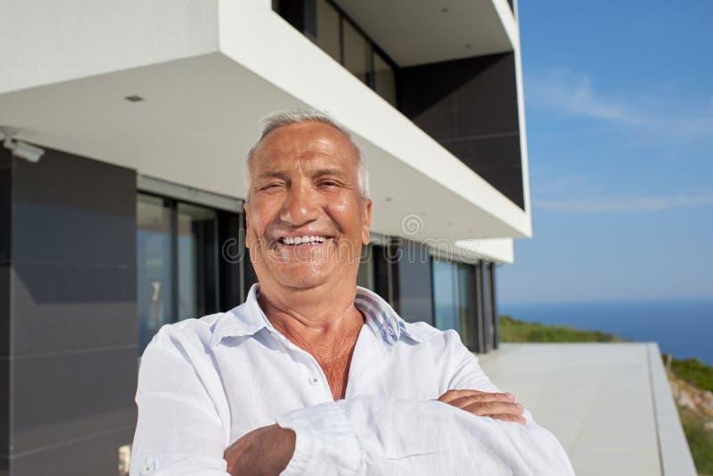 Hogere mens voor modern huis royalty-vrije stock afbeeldingen