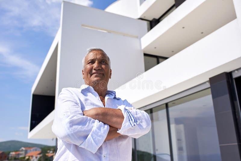 Hogere mens voor modern huis stock afbeelding