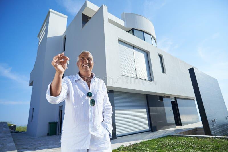 Hogere mens voor modern huis stock fotografie