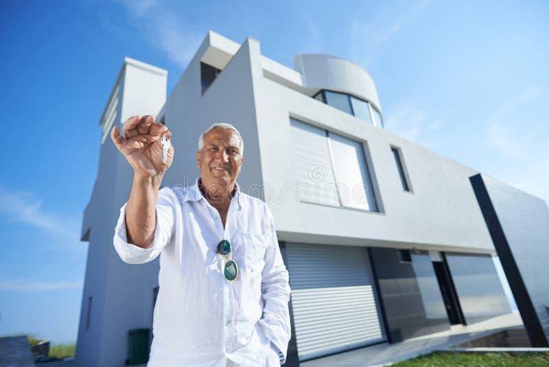 Hogere mens voor modern huis stock foto's