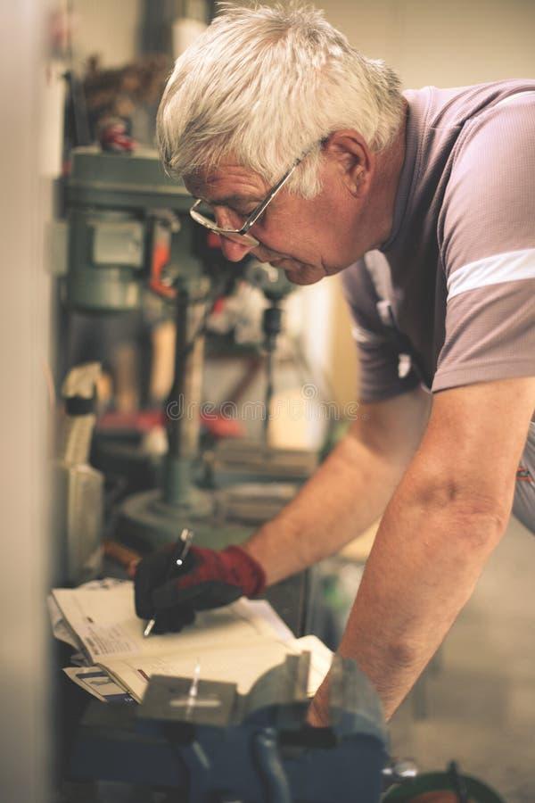 Hogere mens in workshop stock fotografie