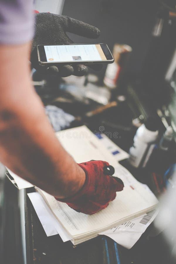 Hogere mens in workshop Mens het schrijven verplichtingen in zijn nota's royalty-vrije stock fotografie