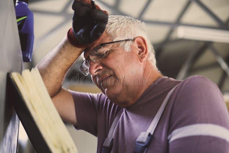 Hogere mens in workshop Ongerust gemaakte mens die zijn ontwerper lezen stock foto's