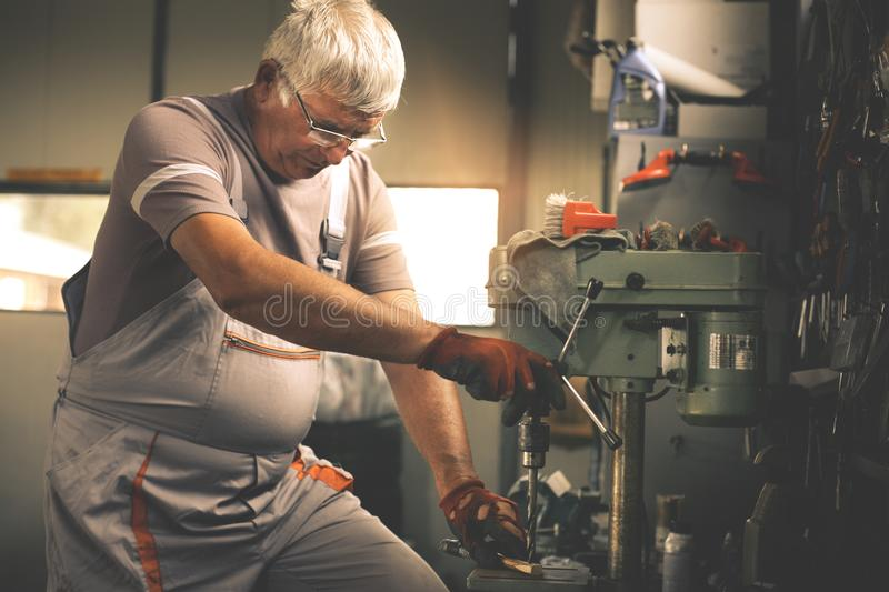 Hogere mens in workshop Timmerman die in garage werken stock fotografie