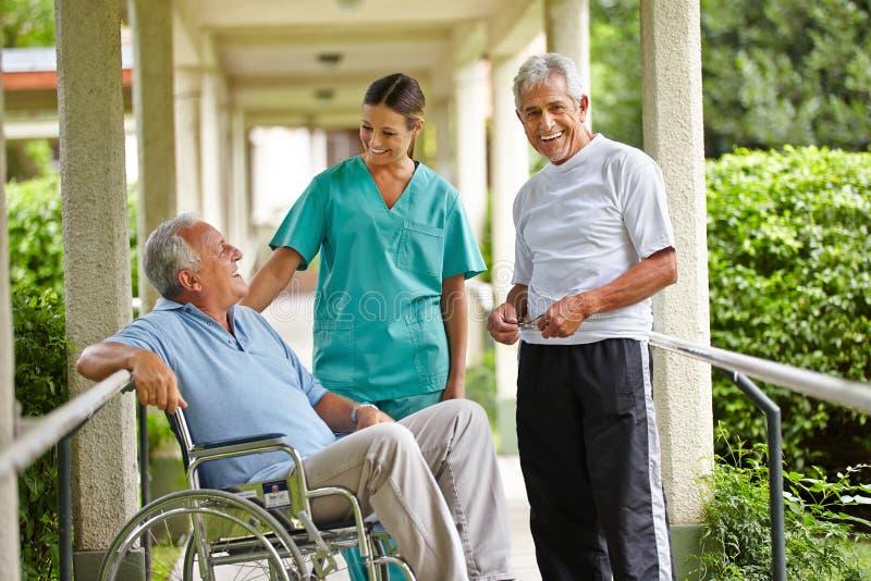 Hogere mensen die aan verpleegster nemen royalty-vrije stock afbeelding