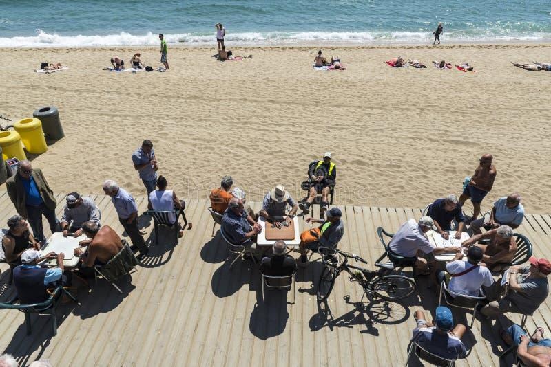 Hogere mensen die domino's op het strand, Barcelona spelen royalty-vrije stock afbeeldingen