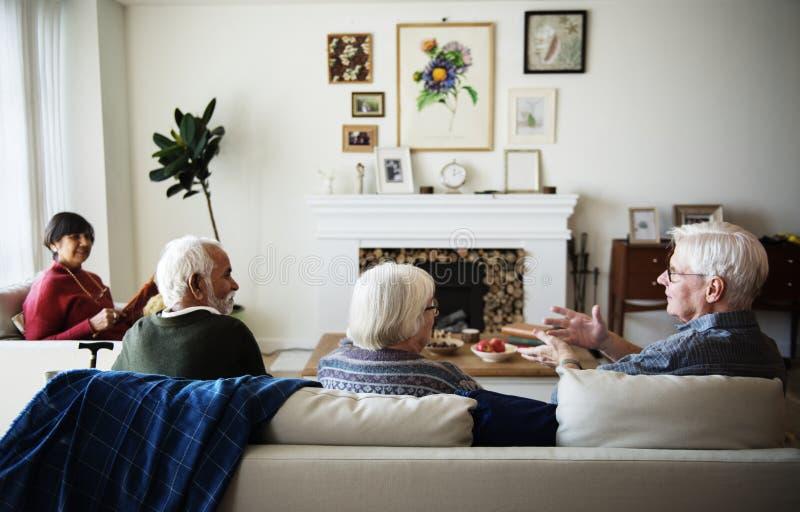 Hogere mensen die in een woonkamer spreken royalty-vrije stock afbeeldingen