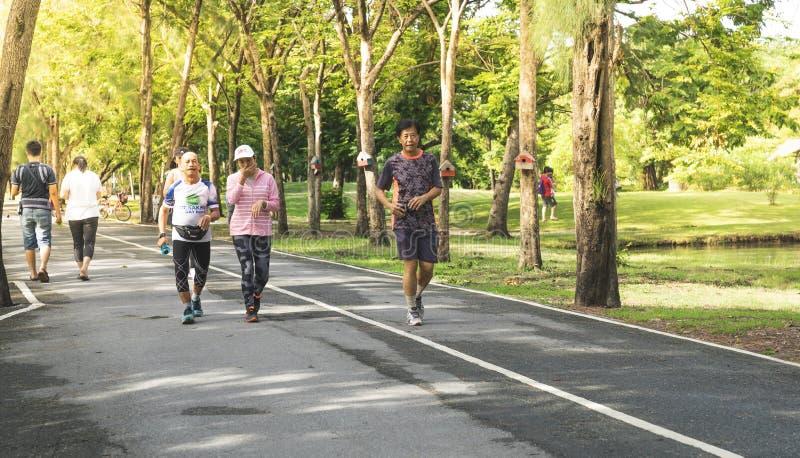Hogere mensen die in groen park in stad lopen royalty-vrije stock afbeeldingen