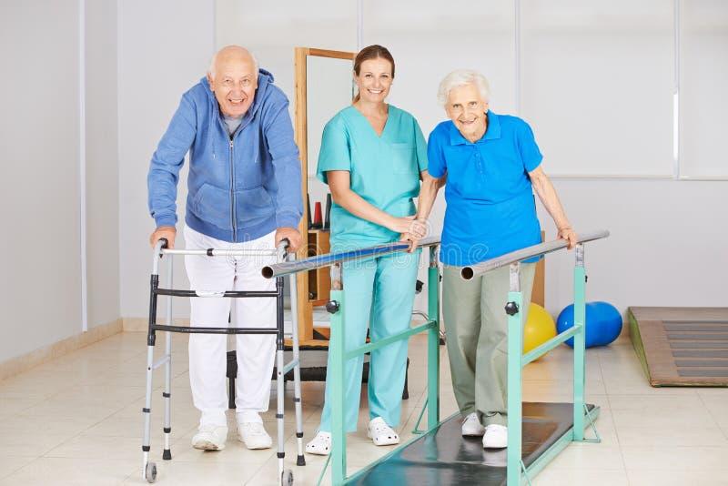 Hogere mensen die het lopen oefening in fysiotherapie doen royalty-vrije stock foto