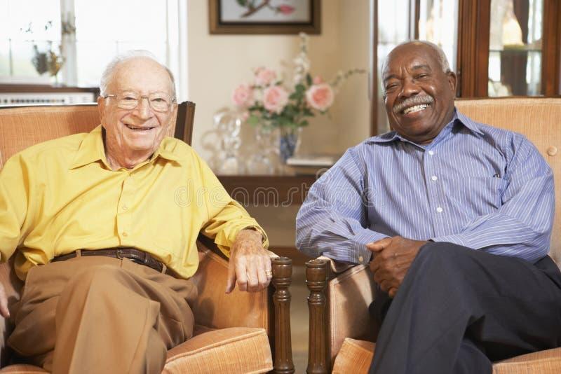 Hogere mensen die in leunstoelen ontspannen stock foto's