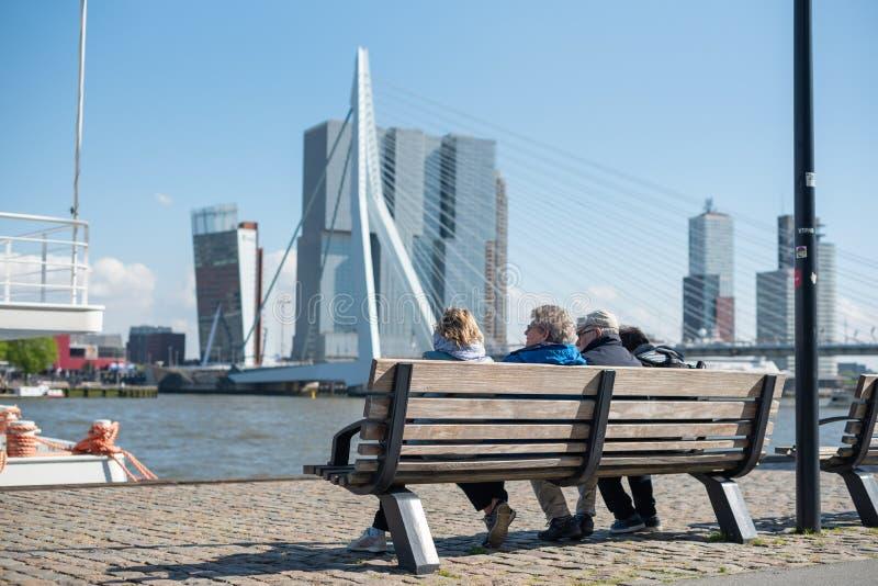 Hogere mensen die op een bank zitten die de horizon van Rotterdam bekijken stock foto