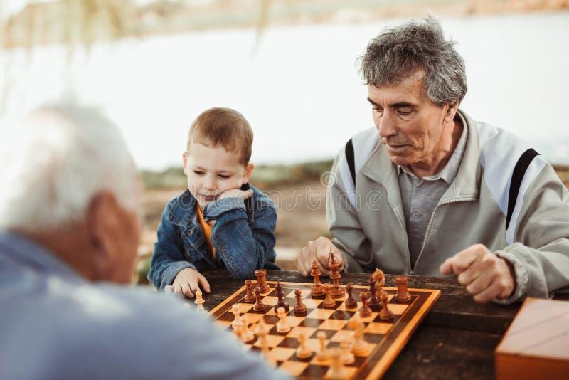 Hogere mensen die pret hebben en schaak spelen royalty-vrije stock foto's