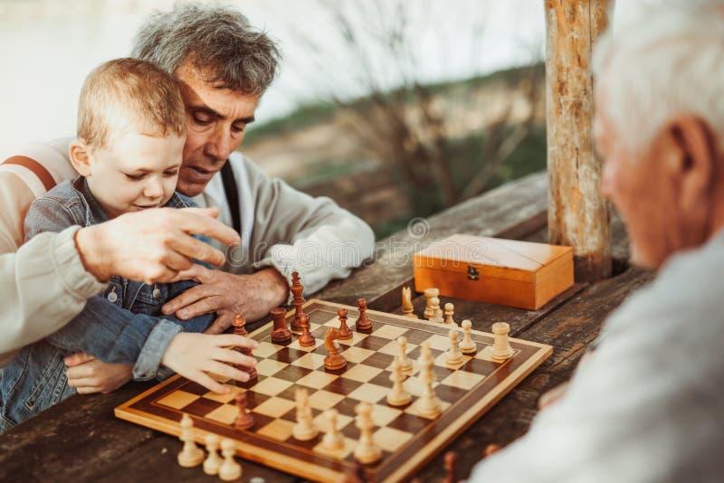 Hogere mensen die pret hebben en schaak spelen royalty-vrije stock afbeelding
