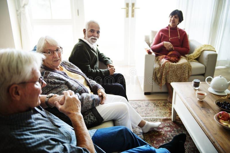 Hogere mensen die samen in een woonkamer zitten royalty-vrije stock fotografie