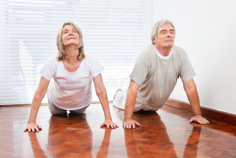 Hogere mensen die yogaoefening doen stock foto's