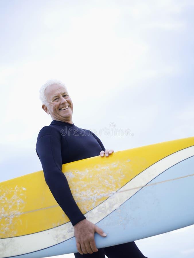 Hogere Mensen Dragende Surfplank royalty-vrije stock foto's