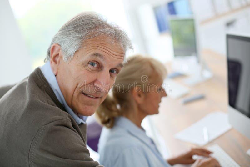 Hogere mensen op kantoor die aan computer werken stock afbeelding