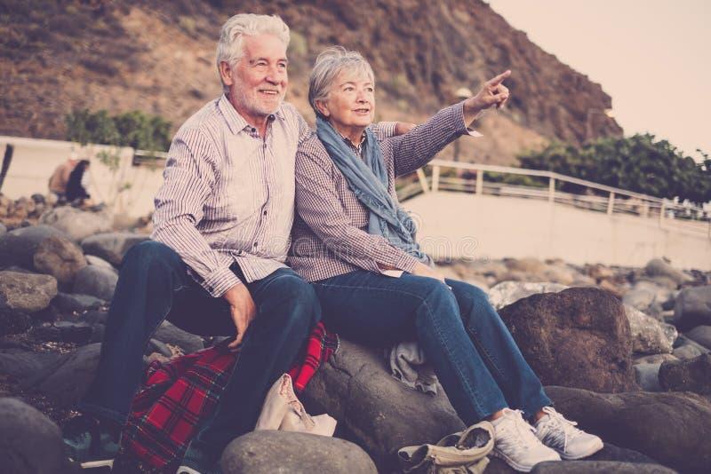 Hogere mensen samen in liefde - Bejaarde paarzitting op het strand die en en met wapen uitgestrekt kijken richten koesteren naar royalty-vrije stock foto's