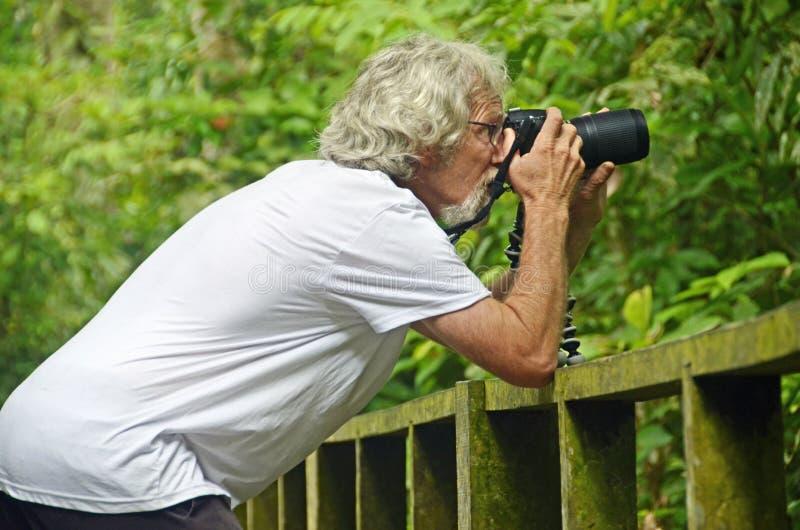 Hogere mensenfotograaf & reiziger die aard & het wildfoto's nemen royalty-vrije stock foto