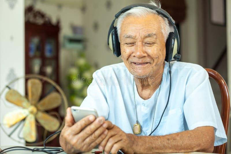 Hogere mensenhoofdtelefoons het Luisteren Muziek thuis stock foto
