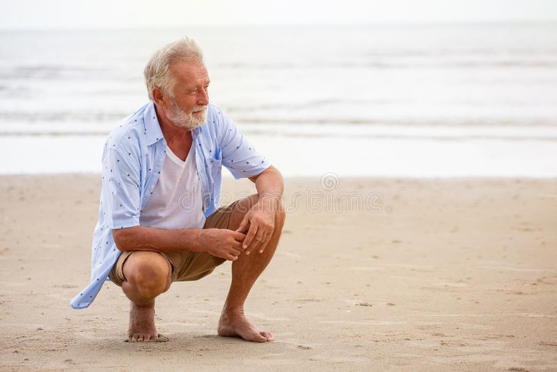 Hogere mensenzitting bij strand het ontspannen Gelukkige teruggetrokken die mens op zand in openlucht wordt ontspannen royalty-vrije stock foto