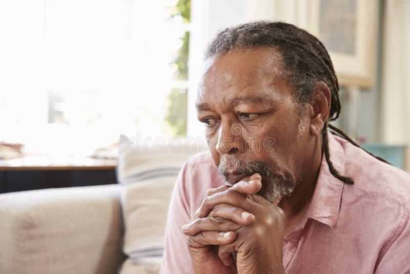 Hogere Mensenzitting op Sofa At Home Suffering From-Depressie stock fotografie