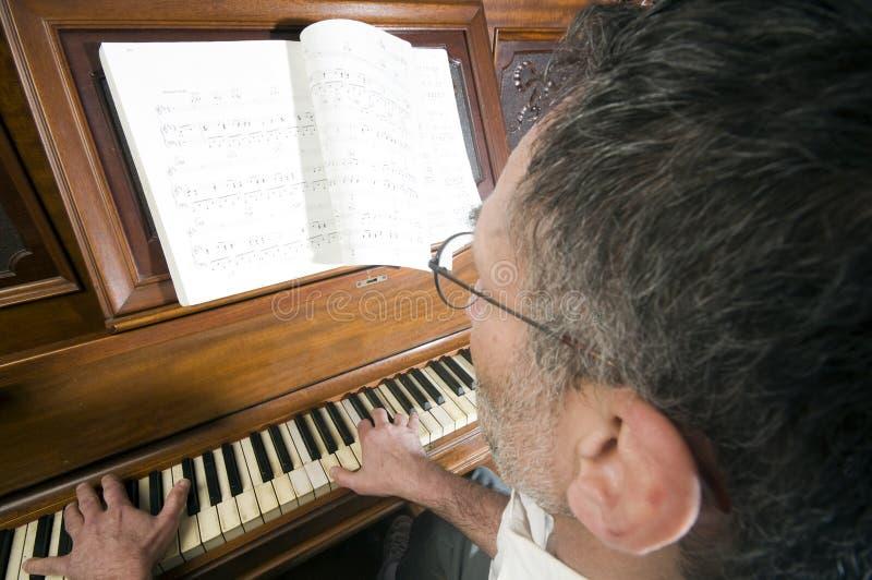 Hogere middenleeftijdsmens het spelen piano stock afbeeldingen