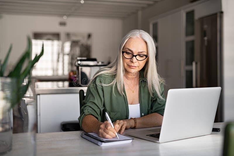Hogere modieuze vrouw die thuis werken stock foto