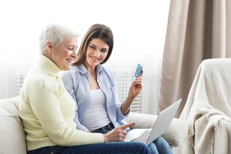 Hogere moeder die online met haar dochter winkelen royalty-vrije stock afbeelding