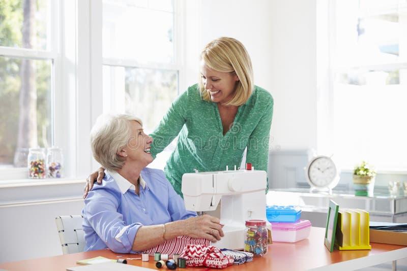 Hogere Moeder en de Volwassen Naaimachine van het Dochtergebruik thuis royalty-vrije stock fotografie