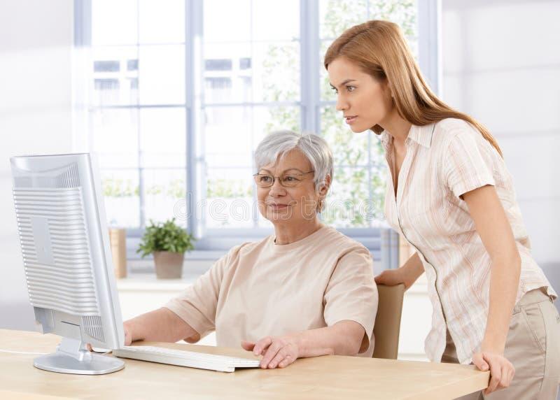 Hogere moeder en dochter die computer met behulp van stock fotografie