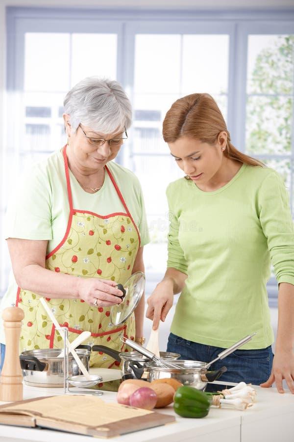 Hogere moeder en dochter die samen koken stock foto's