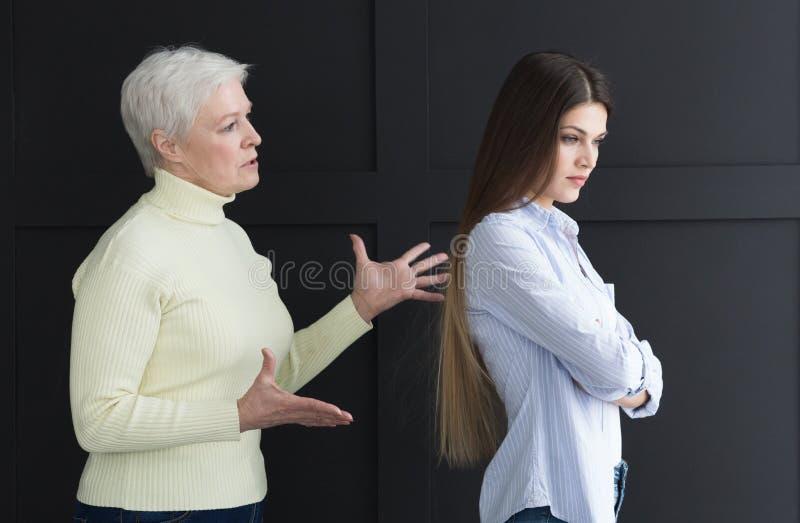 Hogere moeder en dochter na ruzie, zijaanzicht royalty-vrije stock foto