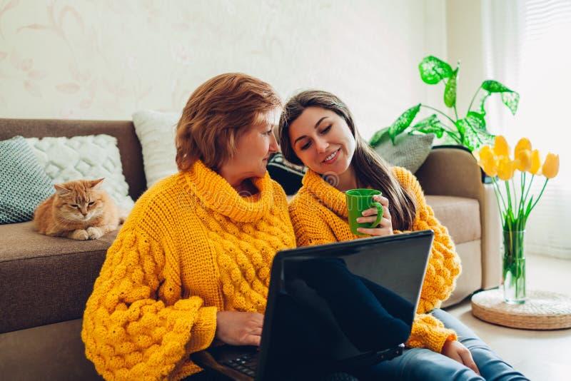 Hogere moeder en haar volwassen dochter die laptop met behulp van thuis terwijl drinkende thee De dagconcept van de moeder ` s royalty-vrije stock afbeeldingen