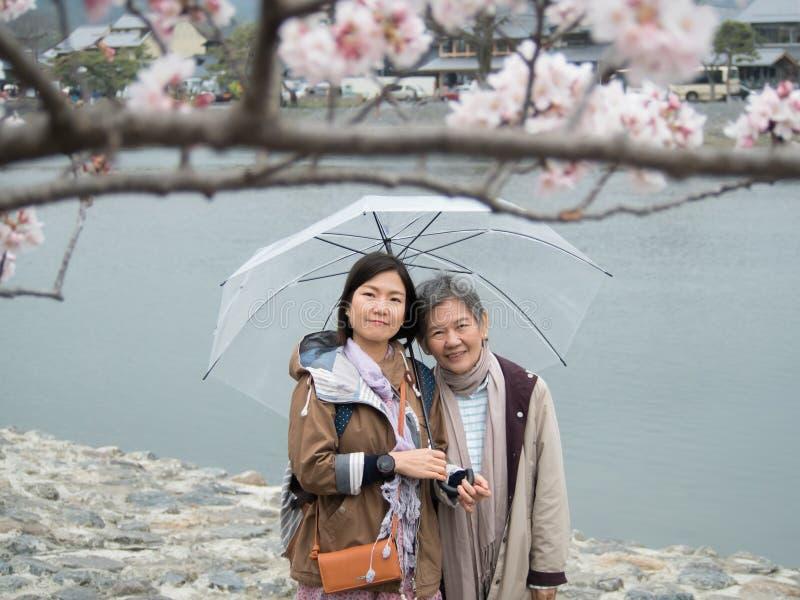 Hogere moeder en volwassen dochter met paraplu royalty-vrije stock foto