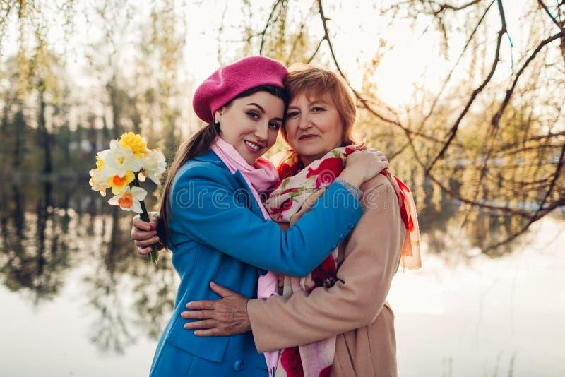 Hogere moeder met bloemen en haar volwassen dochter die door de lenterivier koesteren De dagconcept van de moeder ` s Familiewaar royalty-vrije stock afbeeldingen