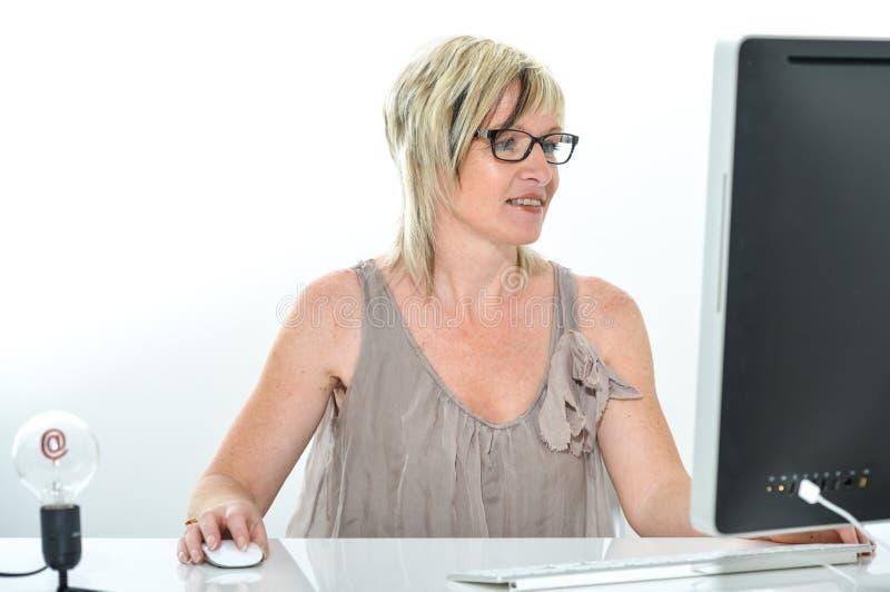 Hogere mooie jonge vrouw die op kantoor met computer werken royalty-vrije stock afbeelding