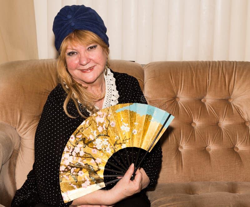 Hogere mooie vrouw met handventilator stock fotografie