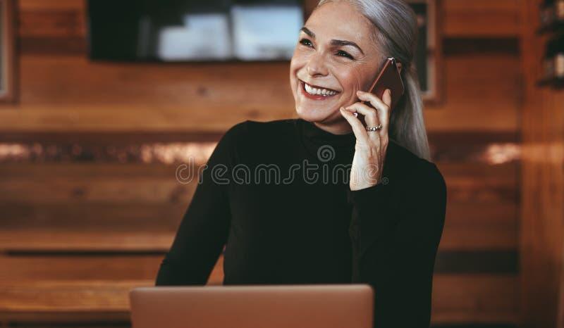 Hogere onderneemster die bij koffiewinkel een telefoongesprek maken stock fotografie