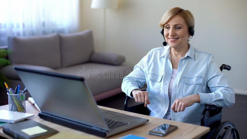 Hogere onderneemster in rolstoel die in bureau, videoconferentie online werken royalty-vrije stock foto's