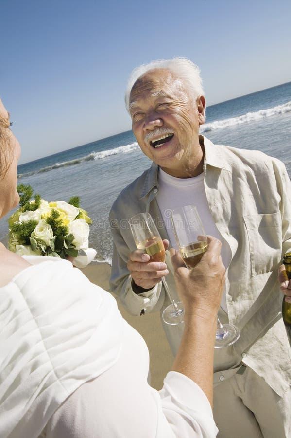 Hogere onlangs weds roosterende champagne bij strand royalty-vrije stock afbeeldingen