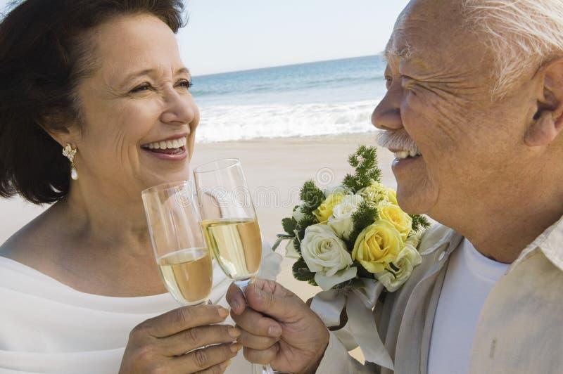 Hogere onlangs weds roosterende champagne bij strand (close-up) stock foto