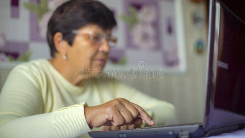 Hogere oude vrouw die in oogglazen Internet op laptop thuis met vrije ruimte en exemplaarruimte surfen royalty-vrije stock afbeeldingen
