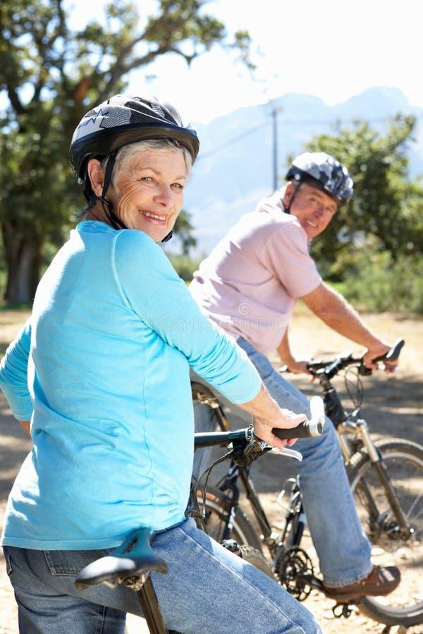 Hogere paar berijdende fietsen die pret hebben stock afbeeldingen