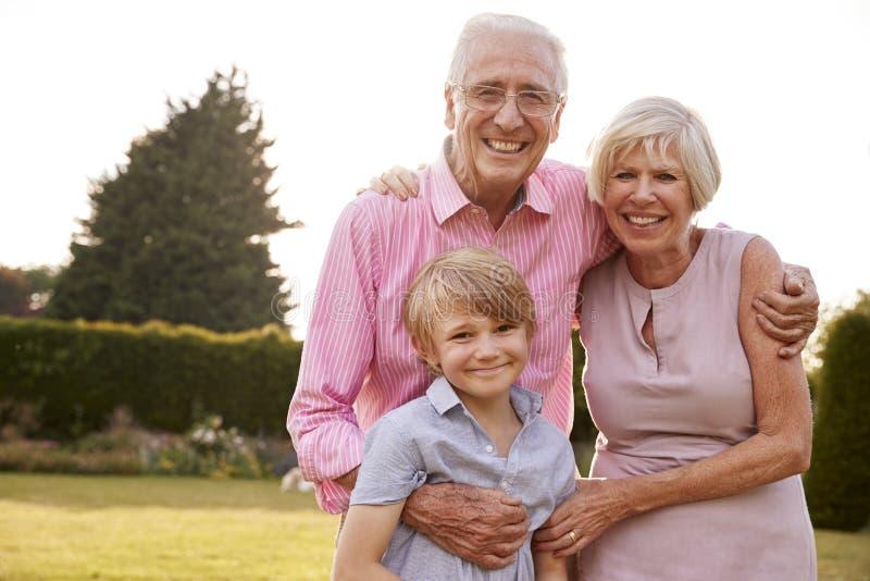 Hogere paar en kleinzoon die en aan camera omhelzen glimlachen stock foto's
