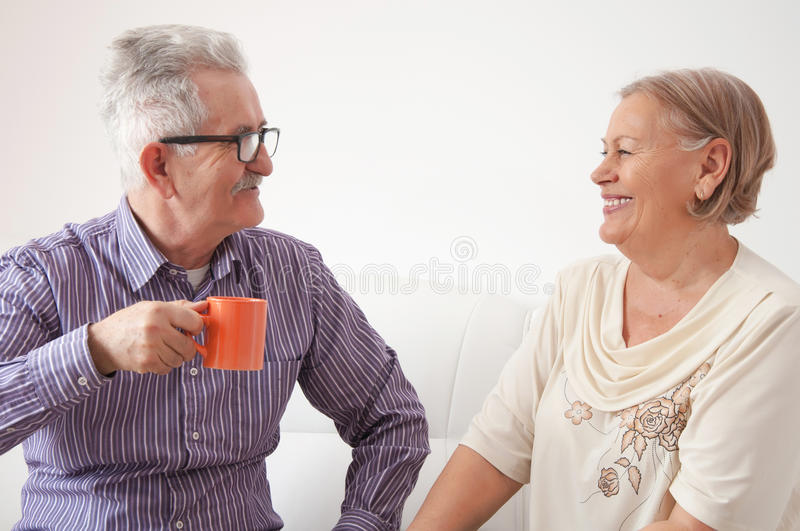 Hogere paar het drinken thee en gelukkig het babbelen stock afbeelding