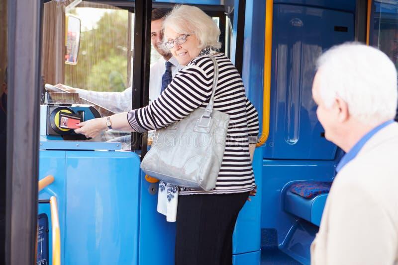 Hogere Paar het Inschepen Bus en het Gebruiken van Pas royalty-vrije stock afbeelding
