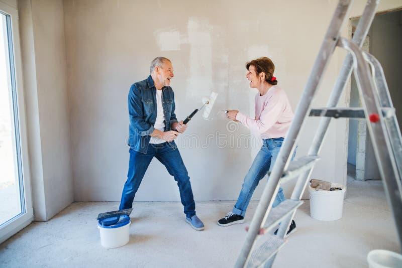Hogere paar het schilderen muren in nieuw huis, dat pret heeft Verhuizingsconcept royalty-vrije stock afbeelding