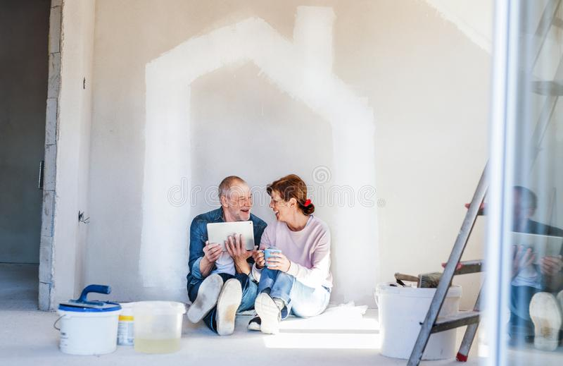 Hogere paar het schilderen muren in nieuw huis, die tablet gebruiken Verhuizingsconcept royalty-vrije stock afbeelding