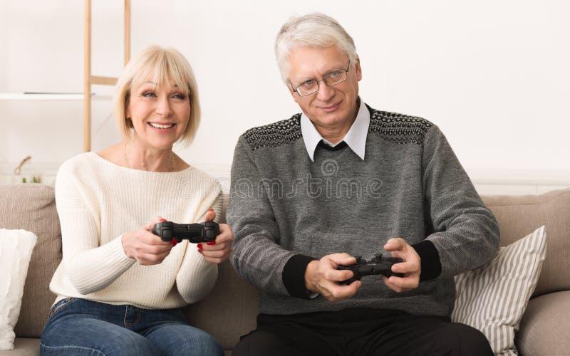 Hogere paar het spelen videospelletjes, die pret hebben royalty-vrije stock afbeeldingen